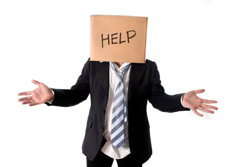 Business man asking for help with carboard box on his head isolated on white background