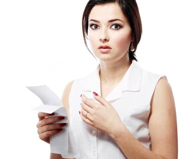 young woman shocking after checking over the receipt in her hands and spending too much