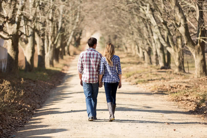 30591900 - rear view of couple holding hands walking in autumn countryside