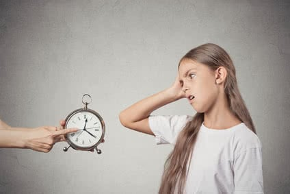 Kids time to go to bed. Portrait mom showing daughter clock that it is late. She doesn't like isolated grey wall background. Face expression emotions. Difficult parenting concept. Children's schedule