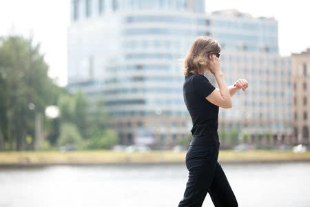 42259184 - young confident business woman walking in hurry, looking at watch, talking on mobile phone on the city street in front of blue glass modern office building beside riverbank, profile view