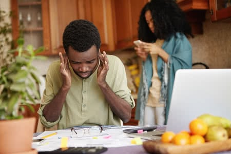 71992997 - young african man plugging his ears, feeling stressed, can't stand financial stress anymore, not able to cover his debts while managing family budget at kitchen table with laptop and lots of papers