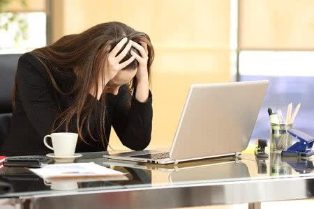 61935138 - desperate businesswoman on line worried after bankruptcy in front of a laptop with her hands in the head at office