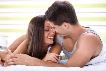 15074999 - love couple lying in bed kissing and looking each other