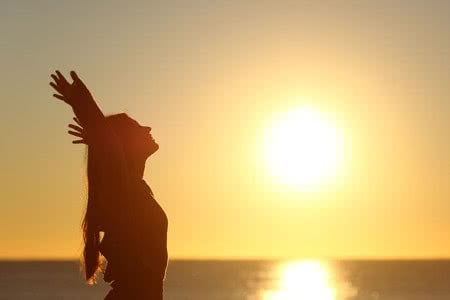 37323219 - woman breathing fresh air at sunset on the beach and raising arms