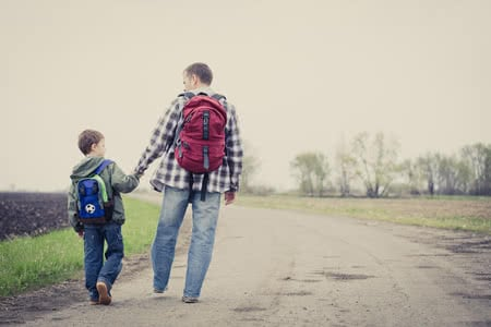 75820836 - father and son walking on the road at the day time. people having fun outdoors. concept of friendly family.