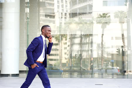 53356513 - side portrait of a happy young man in suit walking and talking on mobile phone