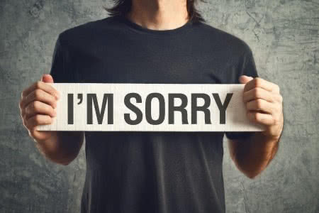 25374459 - man holding i am sorry message on white board. remorse concept.