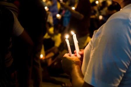 71871585 - group of people holding candle vigil in darkness seeking hope, worship, prayer